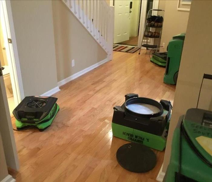 Air movers and drying equipment in front entry of a house