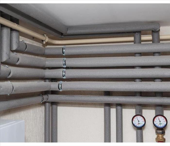 The pipelines in the insulation and pressure gauges flow and return pipes in the boiler room of a private household